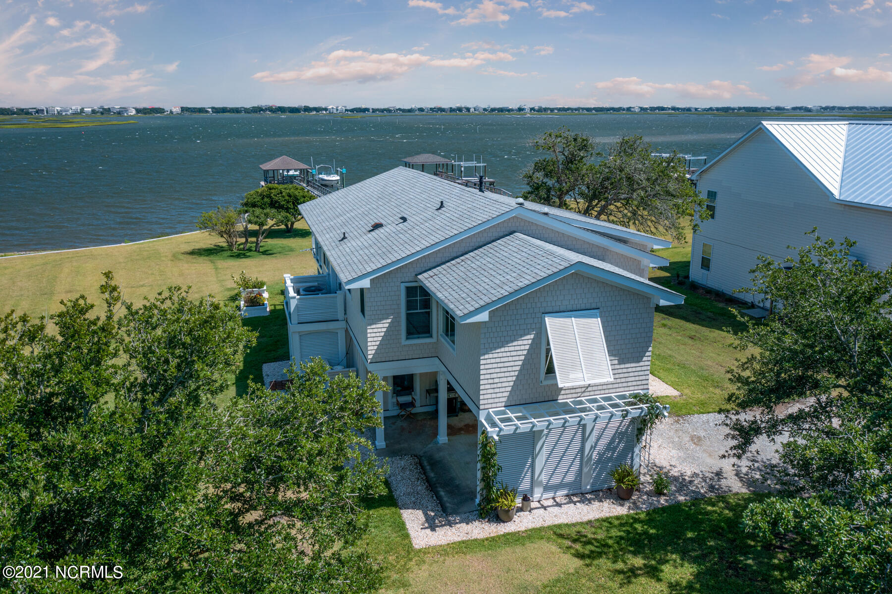 ICW front cottage with gorgeous, unobstructed views of the waterway and Topsail Island!  Located on a large, private .79 acre lot with NO HOA, this one is a rare find!  On the main living level, you will find beautiful hardwood flooring throughout, and lots of large windows showcasing this home's magnificent island views and bringing in tons of natural light. The master bedroom suite is equipped with two closets, solar tubes to brighten up the space, and a newly remodeled master bathroom with heated tile flooring, dual sinks, a large walk- in shower, plenty of toiletry and linen storage, and a spa- like soaking tub with more incredible views of the ICW and the Surf City bridge! A cozy guest bedroom and a full bath are also conveniently located upstairs off the kitchen and family room.  On the bottom level you will find an additional bedroom space also with water views, 2 flex spaces, and another full bathroom.  Enjoy your very own private private pier and dock with two boat lifts (10,000 and 5,000 lbs) and just imagine the ease of jumping in your boat on a whim to fish, cruise, or sandbar hop! Other noteworthy features include:  an outdoor storage shed, a newer bulkhead, a tankless hot water heater, a huge deck overlooking the water with beautiful cable railing, plenty of deck space to dine under the stars, and beautiful crystal gas logs in the family room for those chilly nights at the beach.  The yard is beautifully manicured and spacious and includes garden beds for the perfect spot to grow your own flowers and veggies while watching the boats go by! Paradise found!