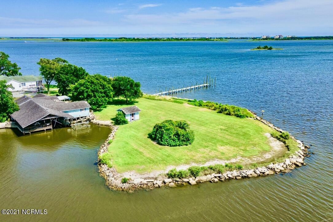 Captivating panoramic waterfront views and serene ocean breeze is what you will experience at this incredible property. This extraordinary .95 acre property has 654 feet of breathtaking shoreline!Rare opportunity to purchase almost an acre of WATERFRONT land with an existing 1,800 sq ft home, pier, and extensive covered dock/decking and boat lift prime and ready for your repairs/renovation! From your private pier and dock as well as your covered boat lift/slip, you will have direct access to Chadwick Bay, New River Inlet, the Intracoastal Waterway, Topsail Beach, Onslow Beach, and the beautiful Atlantic Ocean!  This incredible waterfront retreat is on almost a full acre of prime waterfront land in a park-like setting with mature trees, privacy, and no HOA.Deed included deeded oyster bottom. See Documents attached to this MLS listing. Appointment Required. Do not enter the property or walk the land without a confirmed appointment.