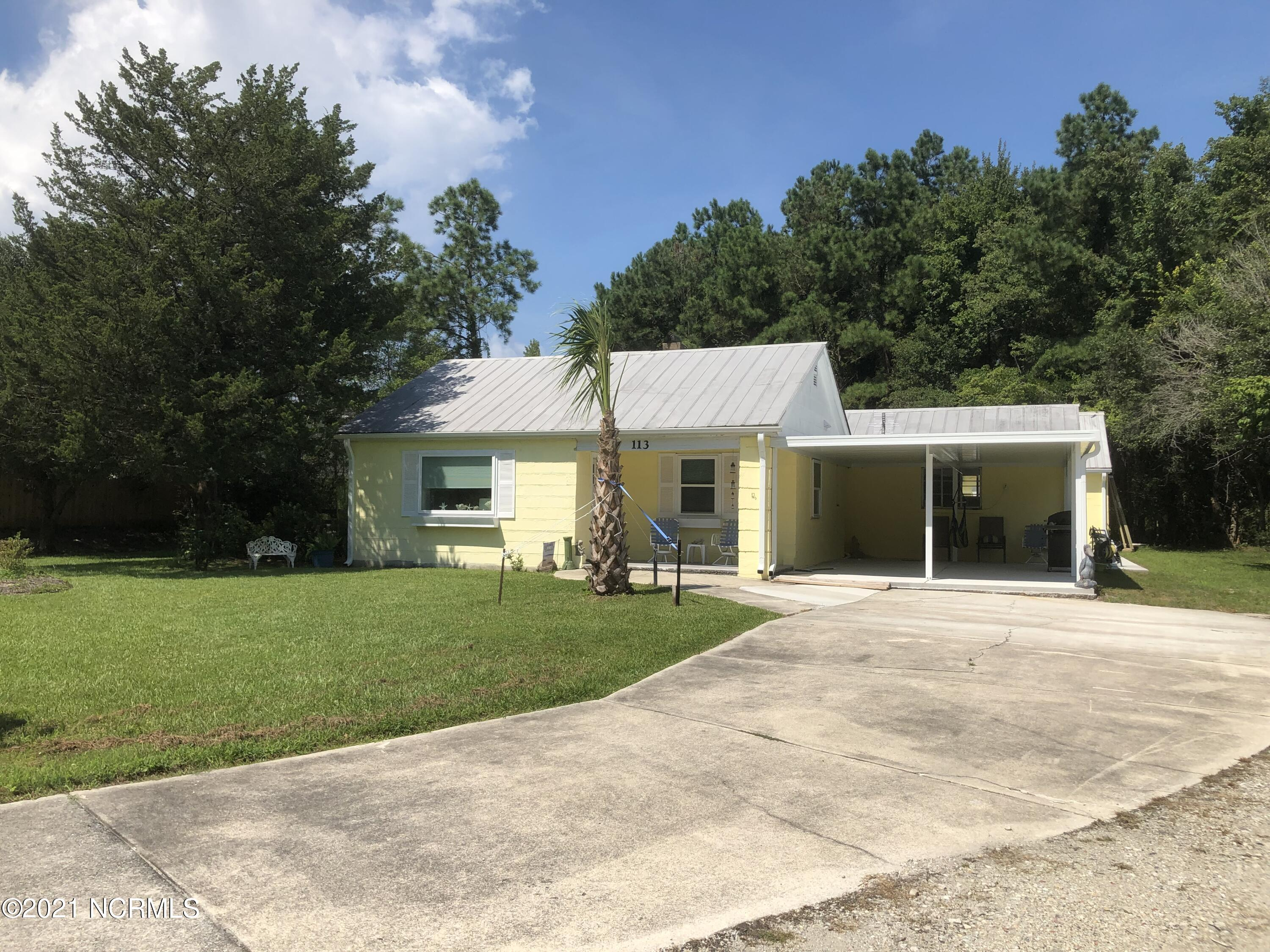 This 2 -3 bedroom house was built to withstand hurricanes in this coastal town with it's concrete block construction and metal roof! Home has recently been renovated and has new appliances . Has 2 carports and nice workshop building out back. Close proximity to the area beaches make this home attractive as a ''get away''! Added plus is the four acres that are included! Great potential.