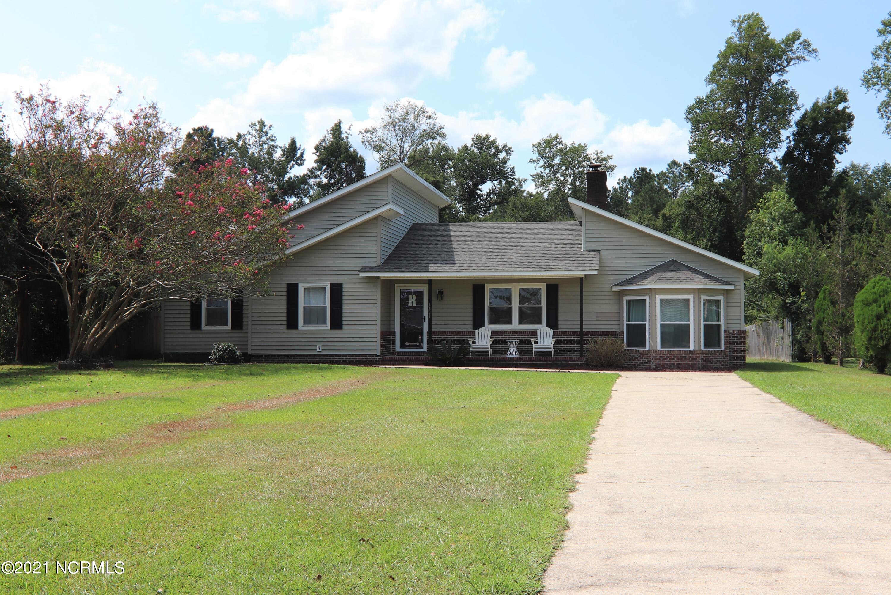 Home Sweet Home!  Are you looking for plenty of space and a large yard?  Thinking of getting chickens or goats?  Then, don't miss out on this 3-bedroom ranch style home situated on over a half-acre with a large bonus room and storage shed! Conveniently located near Camp Lejeune gates, shopping, restaurants and beaches.  Best of all, there's NO city taxes or HOA! As you pull into the driveway, you'll be welcomed by the home's unique and stylish design along with simple but elegant landscaping. The colorful flowers on crepe myrtle tree will catch your attention as you head onto the inviting covered front porch.  Step inside onto beautiful laminate flooring that flows throughout the main living area.   The living room features a floor-to-ceiling brick fireplace that's perfect for warming up on those chilly evenings.  The hallway to the left leads to 3 bedrooms and 2 full bathrooms, with the master bedroom and bathroom in the back of the home. From the living room, you'll enter the kitchen and find attractive white cabinets, a stainless-steel stove and dishwasher along with an upgraded faucet and black refrigerator.   Lovely French doors, that open up to the big backyard, allow lots of natural light to pour into the dining room. Off the dining area is a large bonus room that's perfect to use as a gym, play area or second living room!The storage shed in the back offers plenty of extra storage space.  The backyard offers privacy as it's partially enclosed with a 6-foot wooden privacy fence.  The yard continues behind the fence to offer space that's perfect for chickens or a garden!  Schedule a showing today before this one's gone!