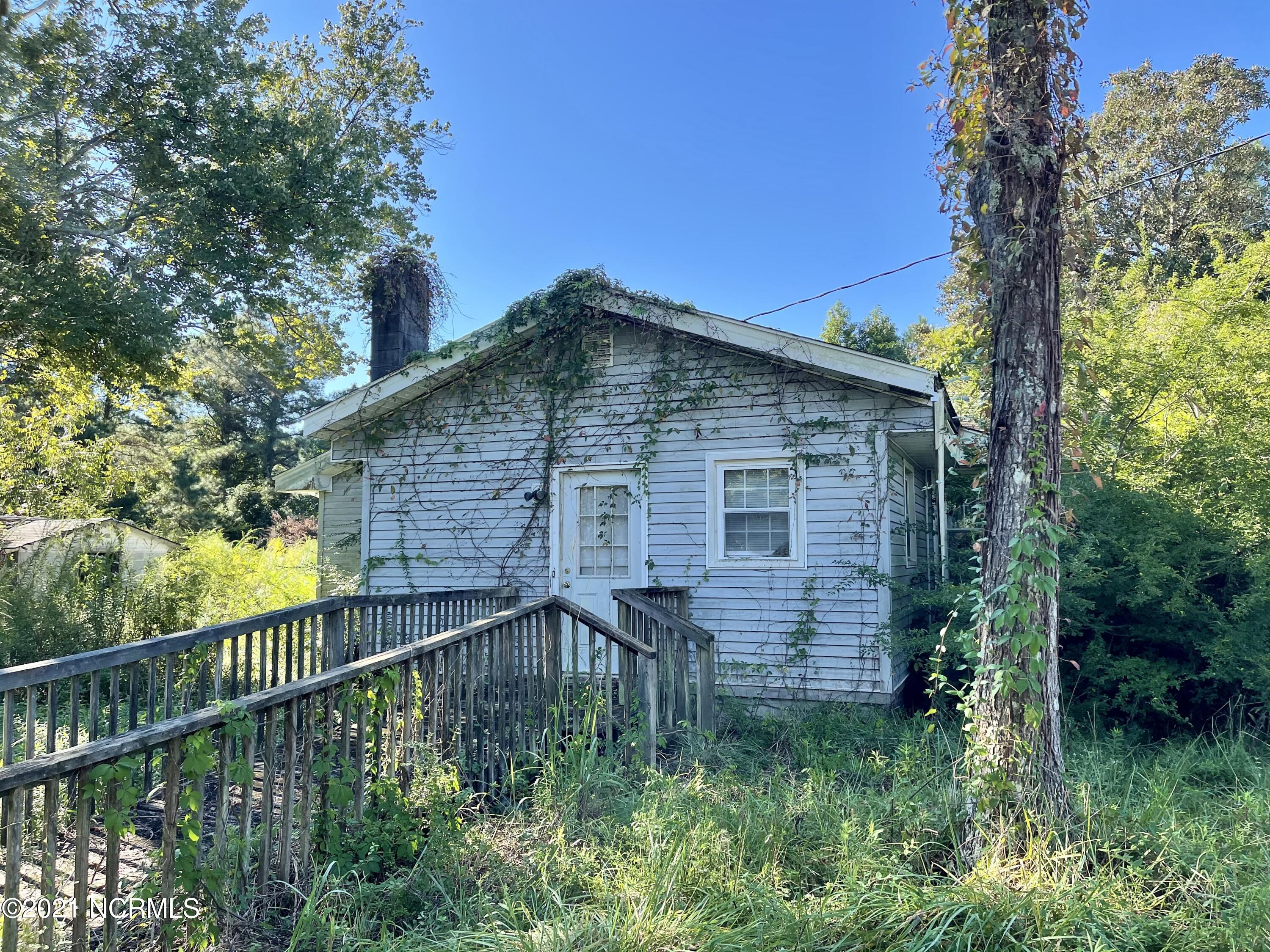 Great Location! 1.5 acres by Mill Creek Rd and Hwy 50, less than 5 miles from the Surf City bridge. Land Value only, Property will be sold ''As Is'' no repairs will be done.  455 ft of Road Frontage on NC Hwy 50. Existing home has not been lived in for several years. There are partial outbuildings. The structure to the left used to be a Country Store. Just minutes to Topsail Island