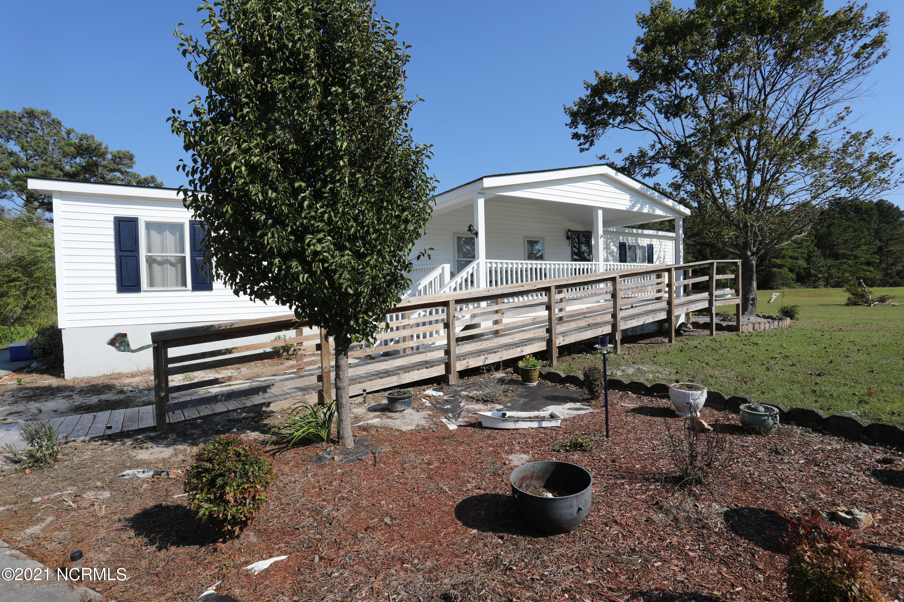 This three bedroom, two bath home is located just across the bridge form Emerald Isle, and just over 3 miles from the Wildlife boat ramp. Home sits on .66 acres of beautiful land.  The 20x25 workshop located in back has 2 covered storage areas, power, water, and a wood stove.  Inside the home has an open floor plan with wood flooring and a sunroom that can be used as an office.  The entrance is lined by trees.  There is a shallow well for watering, updated windows and A/C, a newer roof and updated siding and a concrete raised foundation.  Billboard rental income $1800/year.  A must see!