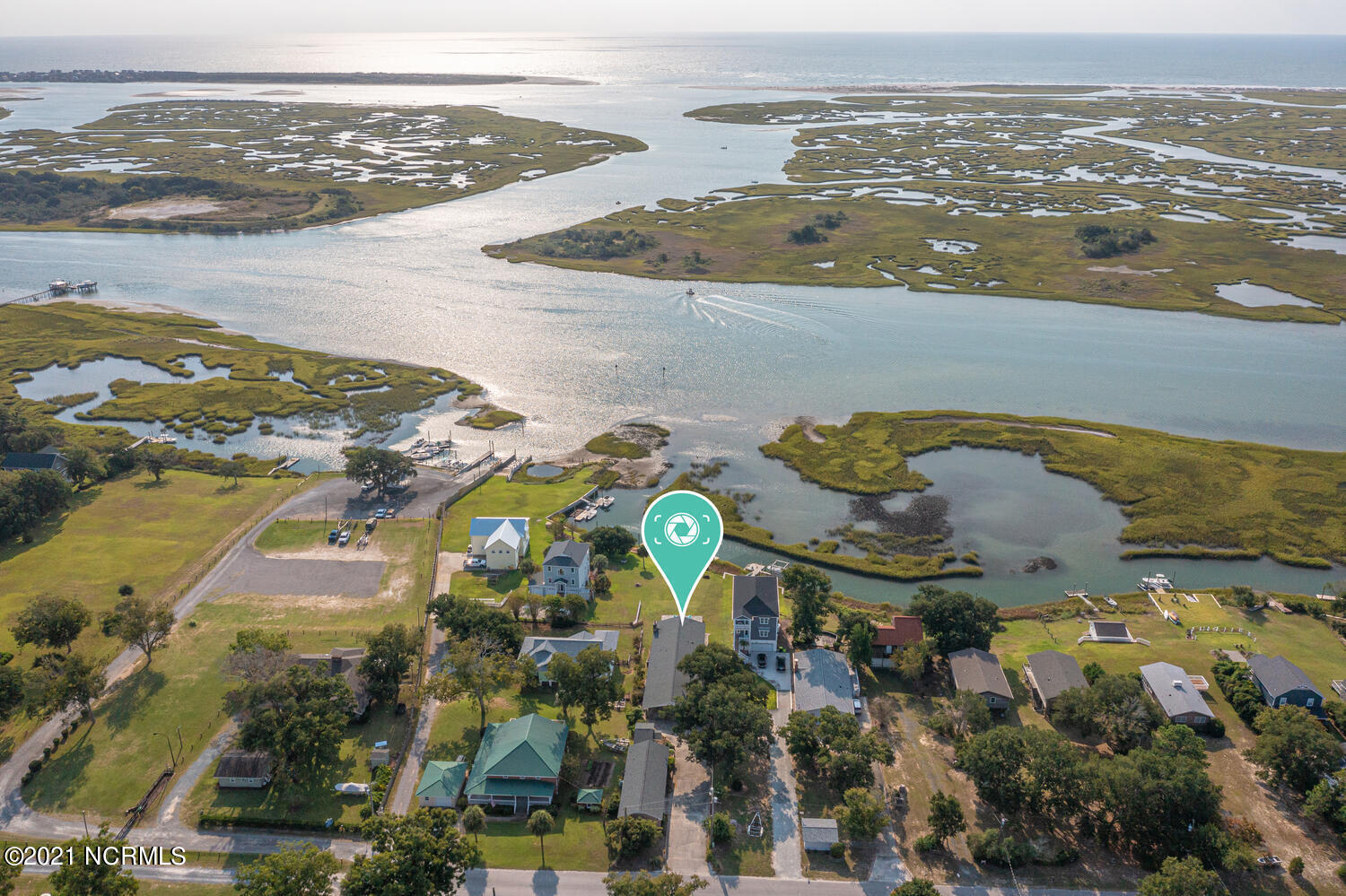 Hands Down, the best views in Hampstead, along with one of the most unique properties found in our area. This charming, waterfront, brick ranch sits upon a high bluff ''Not in a Flood Zone'', overlooking New Topsail Inlet, The Intra Coastal Waterway, Beautiful Marsh Islands, and most impressively The Atlantic Ocean. Yet, that's just the beginning. This home has a detached, one bay garage with a large storage room, plus 670 heated sqft (2 room studio with a full bath), AND an additional 3rd dwelling with 205 heated sqft, which is the perfect Art Studio/She Shed ''plumbed for an additional full bath''. The main house has an attached 2 car garage as well as an attached 2 car carport/boat storage.. given its height. Inside the main residence, you will find hardwood floors, an open floor plan, kitchen with granite countertops, a large granite bar, gas range, a gas fireplace accented with white brick, and of course the proper mantel piece.  Furthermore, one of the most dazzling assets to this home, is the plethora of windows located on the back of the home, lining the main living area, and flowing natural light through the kitchen. Each window boasts breathtaking views of the Sound, ICW, Inlet, and Ocean. Each morning, it's as if Bob Ross himself, paints every window withs its own perfect sunrise over top of a serene, Natural, Coastal North Carolina Waterfront. The boat dock is tucked around a marsh island, giving it the ideal protection from the ICW waves, yet not hindering the convenience of a quick boat ride to any of the private islands across the way. Hampstead Marina/Boat Ramp is only a block away. This is truly a one-of-a-kind property, and in my opinion UNBEATABLE VIEWS.