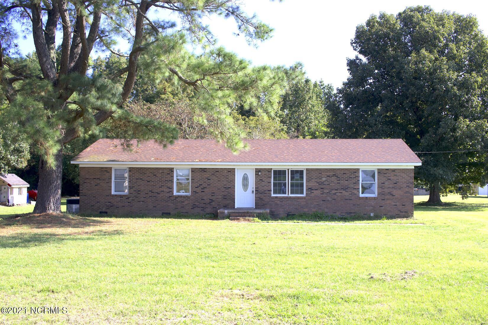 Come see this brick home in a country town just minutes from the Beulaville middle school, post office, grocery stores, and restaurants. This home has an original floor plan that includes 3 bedrooms, 1 and a half baths, kitchen and dining room combo, a carport in the back, plus a garage with a back entrance. This house has a roof that was replaced in 2019 by the previous owner, updated floors in the living room, kitchen and hallway, as well as two new windows in the living room, plus a new front door. In the bedrooms you will find the well-maintained original pine wood floors with reasonable closet space and new blinds. This home has been freshly painted and professionally cleaned. The garage is not included in the house square footage but you have approximately 300 square feet of extra space to park a vehicle, make a home gym, or use as storage space. The laundry room is also located in the garage to maximize your living space. This charming home could be a great investment property or perfect for the first-time home buyer who is willing to put in a little bit of sweet equity.