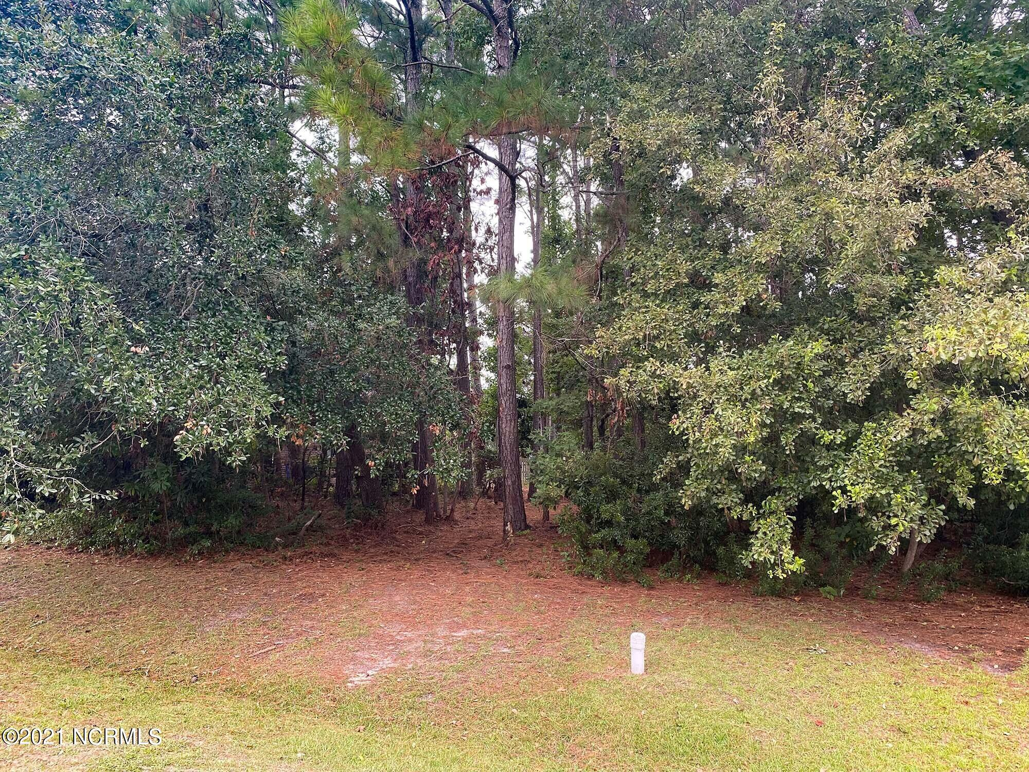 Cul-de-sac lot located in the golfing community of North Shore Country Club, minutes to the beautiful white sand of North Topsail Beach. Measuring .36 acres, this wooded lot is ready for you to make it your own. It's convenient to shopping and dining, and within walking distance of neighborhood amenities (golf, pool, and tennis), which are available to residents at an additional cost.