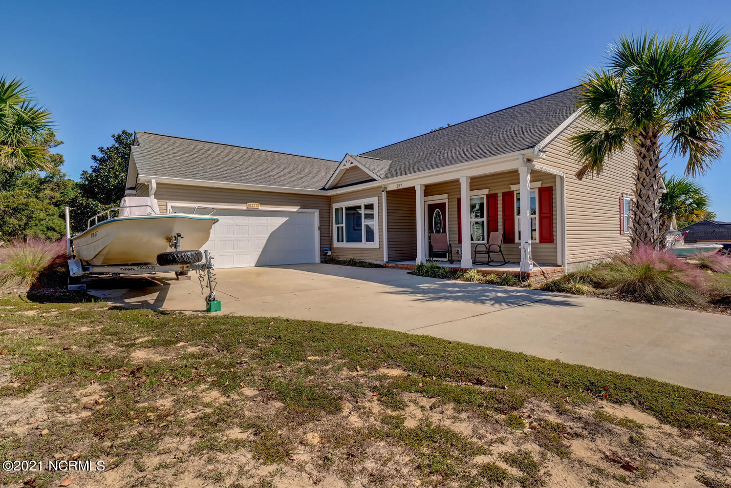 Beautiful, like-new ranch-style home on a spacious .53 acres in the private waterfront community of Topsail Watch in Hampstead with great waterway views from the screened porch. Built in 2017, this 3 bedroom, 2.5 bathroom, 1,889 square-foot home boasts premium finishes in every space including 9' ceilings, granite counters in all the bathrooms, hardwood floors, crown molding, wainscoting, a formal dining room, and plenty of storage options. The tiled gas fireplace and vaulted ceilings enhance the bright and airy open floor layout. Your premier kitchen highlights gorgeous granite countertops, decorative quarry tile floors, stainless steel appliances, a sizable pantry, an island for additional seating, and a sunlit breakfast nook. A half bathroom is conveniently located off the casual dining area. A laundry room with built-in shelving is off the kitchen near the pantry and garage entrance. Enjoy watching the sparkling Intracoastal Waterway from the privacy of your spacious screened porch or soak up the sun on your expansive back deck. Your impressive master suite features a tray ceiling, granite countertops, custom tiled walk-in shower, corner soaking tub, large walk-in closet, separate vanities, two convenient entrances, and private access to the screened-in porch. On the other side of the house are two spacious bedrooms and the second full bathroom with granite countertops. With .53 acres, you can enjoy yard games, cookouts, and more with friends and family or simply take in the peaceful Carolina seaside. Other features include a two-car garage, transfer switch for generator, and convenient walk-up stairs to the attic from the breakfast nook. A short stroll to launch your kayak in the Intracoastal Waterway for quick access to Topsail Island and all the surrounding islands and inlets. You'll be singing Sweet Carolina in this beautiful home in the quiet waterfront community of Topsail Watch. Call today to make it yours!