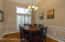 The dining room features teak wood floors and is located off to the left upon entering the home.
