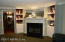 Woodburning fireplace with mantle, display shelves and cabinets