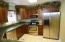 View of beautiful kitchen with cherry cabinets, stainless appliances and quartz counters