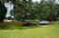 View of back yard with car port/work area and large yard