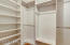Walk in closet with built-in shelves in the master bedroom.