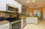 Light bright gourmet kitchen with stainless appliances and tile floors