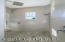 Shower with pebble flooring finish and rain shower head
