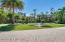 Graceful palm trees and pond accent the paver and concrete driveway .