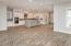 Family room to kitchen view with wood floors stacked cabinets with glss fronts and butlers pantry