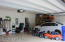 Large 3 car garage with storage shelves.