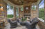 Screened enclosed lanai features stacked stone walls and paneled wood ceiling.