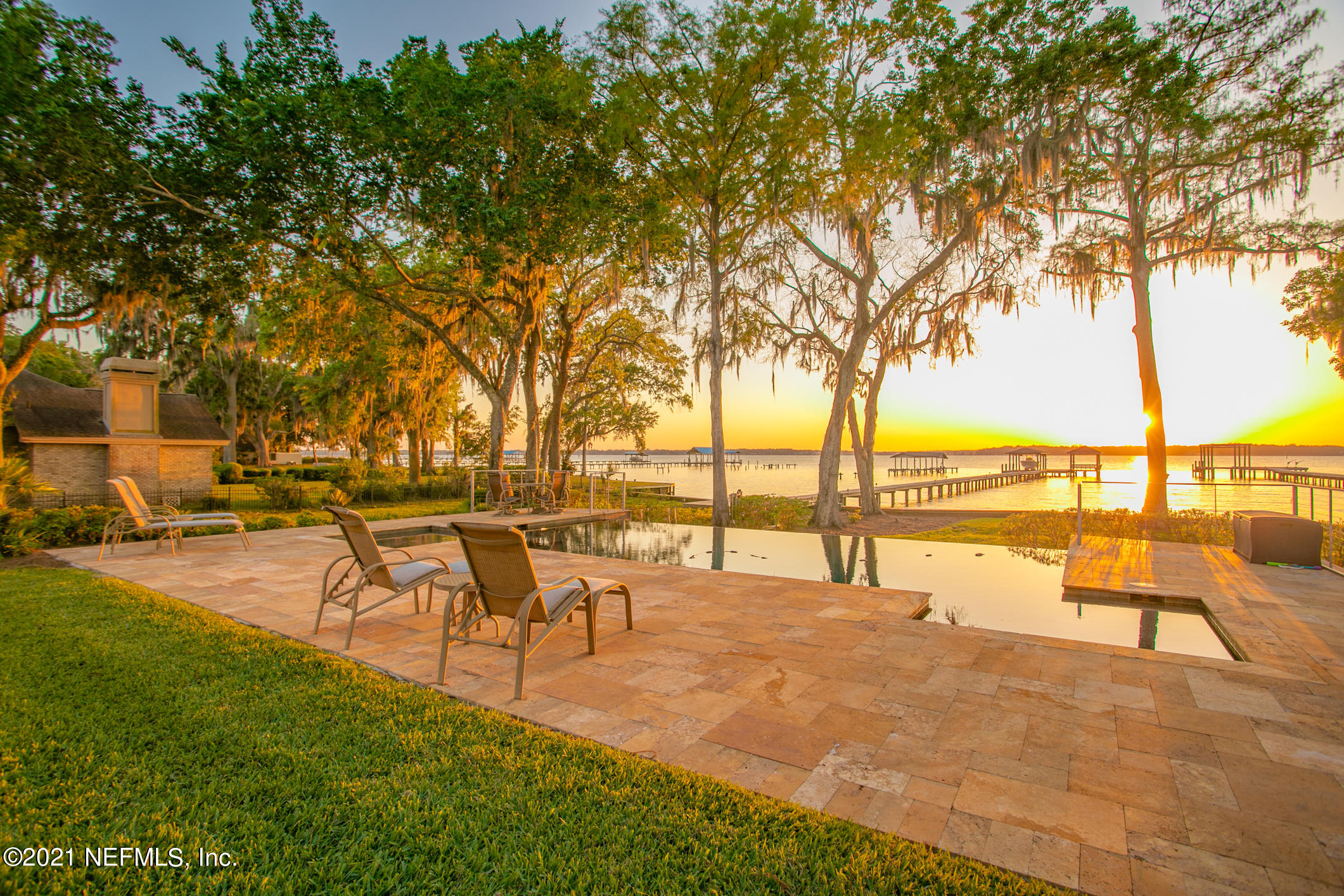 Exceptional St Johns Riverfront unlike any other. This owner has updated and renovated twice since owning the home to the highest level of standards. Doors open out from multiple rooms to the 2 story screened enclosed lanai complete with summer kitchen, 2 raised bars, gas fireplace, TV spaces and a rock waterfall with the ambient sounds of water. All overlooking the gorgeous infinity pool & river... Step back inside where you will find beautiful hardwood floors & coffered ceilings. The kitchen offers cabinets on every wall and a walk in pantry. Family meals enjoyed from the octagonal shaped breakfast room offering river views. Luxury master on 2nd floor with separate parlor and fireplace. Closets and overflow storage galore. Also upstairs is a deluxe home theatre & bar area.5 car garage.