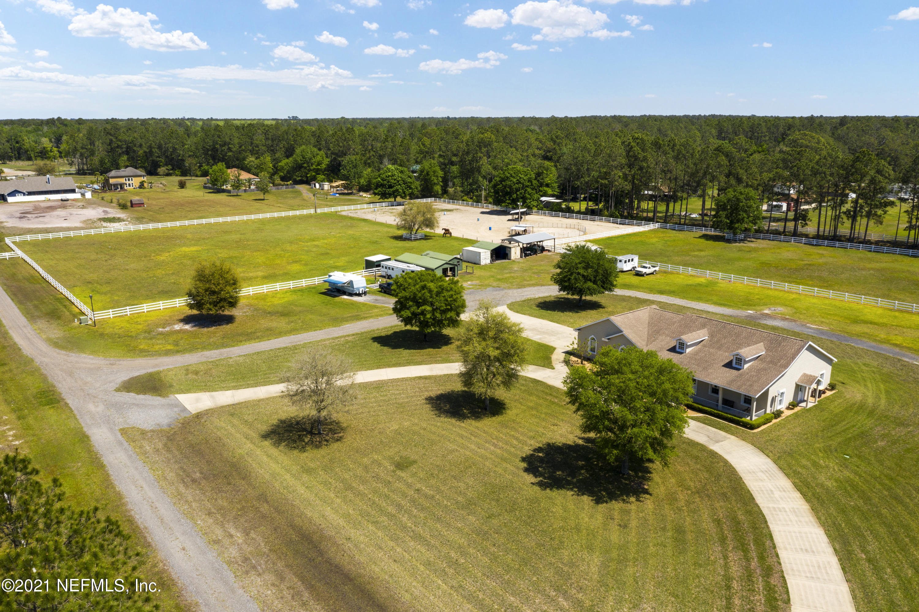 Come see this one of a kind 8 Acre Horse property within 20 minutes of downtown Jacksonville! It comes with a lit sand riding arena, 5 stable barn, and a one owner 2305 sq ft house. The house was custom built in 2004 with the builder specs of South Florida. That means that every wall is filled concrete block from foundation to the roof line and the roof is a hearty 30 year architectural shingle. The 2 car garage is oversized with 9 foot doors and 10 foot ceilings with more than 30ft of depth. The inside of the home is also well appointed with 10ft ceilings throughout with a vaulted ceiling in the living room and a trey ceilings in the dining room and master bedroom. The kitchen has quartz counters and a full gourmet double oven stainless steel appliances with 42'' original maple cabinets. The master bedroom has private access to the covered porch, his and hers closets, separate shower with jetted bathtub, and a double vanity. The interior also has wired speakers throughout the home and a full interior laundry room. On the covered porch is a full outdoor kitchen with sink and it's electronically prepped for a pool. Outside is where the fun begins. The exterior of the home was just recently painted. There is a powered sprinkler system throughout the property. An RV hookup with power, septic and water. A 5 stall metal barn with a 12x14 insulated tack room and a metal hay barn. The back pasture is 1.5 acres and the other pasture is 2 acres. In the arena, there is water and power at the shelter along with power at the hay shelter. Only 12 miles from Diamond D Ranch and the Equestrian Center. Also, the Jacksonville-Baldwin Rail Trail is just around the corner and a great place to ride. Call today for your showing!