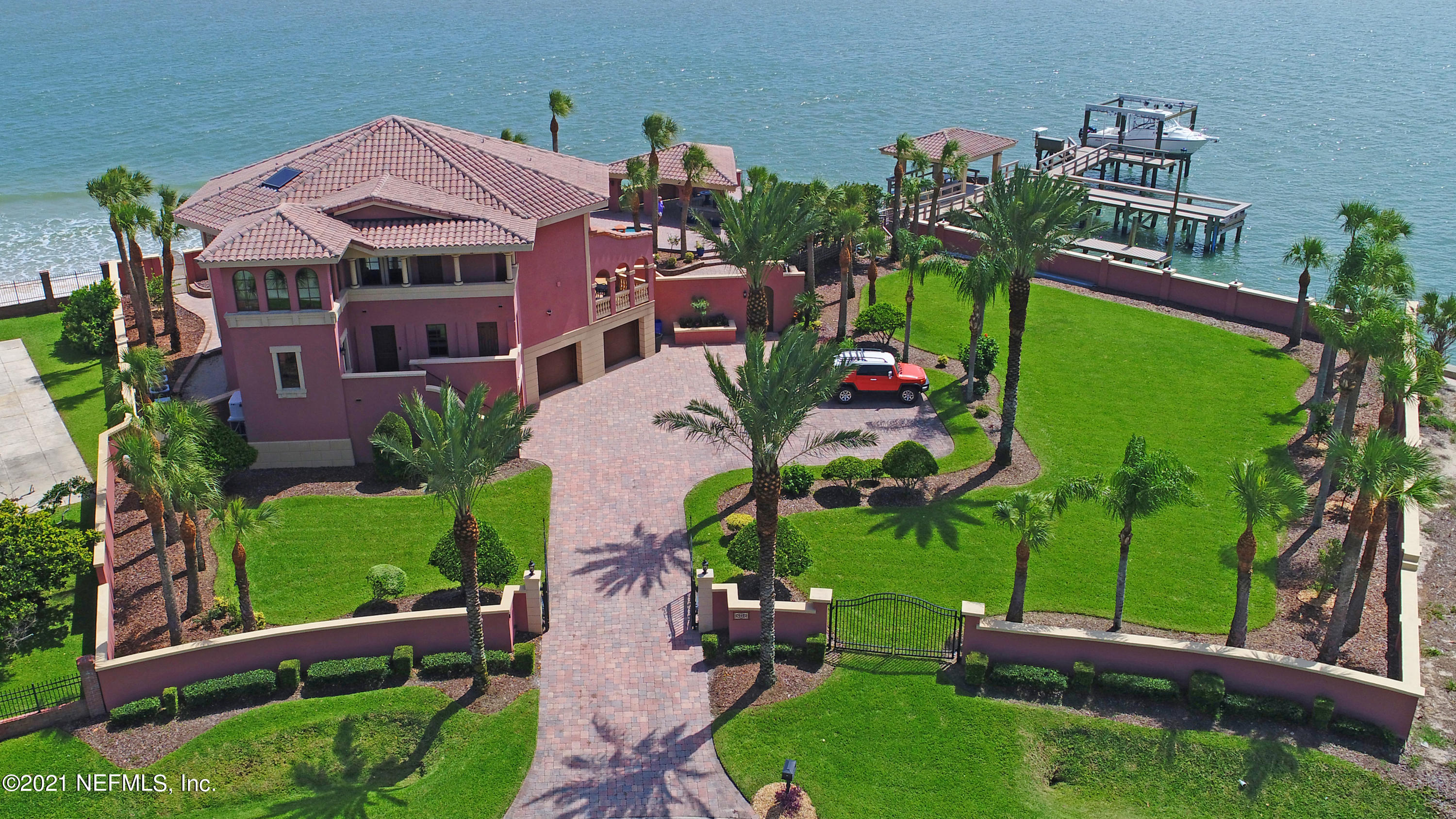 Porpoise Point Luxury Home Location is everything, and this home delivers! The ultimate in resort living with over 180 of breathtaking views of downtown St. Augustine, Castillo de San Marcos, St. Augustine Lighthouse, and the historic cross - all while situated on a rare double lot on the Intracoastal Waterway and the Atlantic Ocean! Water and views are everywhere in sight, and the beach sand, right in your backyard. Privacy and relaxation await as you relax in your custom pool and spa or hop on your boat for a luxurious cruise from your private deep-water dock with a 33,000lb boat lift. Simply put, there is no comparison of amenities and location in all of Northeast Florida. This luxury, gated, three-story Mediterranean style home showcases 5,224 sq. ft. of interior living space built exclusively around the views with an additional 2,374 sq. ft. comprised of balconies, terraces, and more. The large corner lot is a private compound secured by concrete walls, decorative steel gates, and a steel-concrete bulkhead surrounding the property. The generous living area has 17' ceilings, features a central stone fireplace flanked by windows and balconies everywhere, and easily connects to the open plan kitchen. There is a large formal dining room, study or art room loaded with sunshine from tall windows, and a private media room. Each of the upstairs bedrooms and study feature a generous size floor plan and private outdoor terrace. Take the central elevator to easily access anywhere in the home. On the ground floor, stop off at the large climate-controlled wine cellar on your way to the entertaining kitchen, outdoor swimming pool, multiple gazebos, and large outdoor bar. This home has all the amenities and is truly an entertainer's paradise!