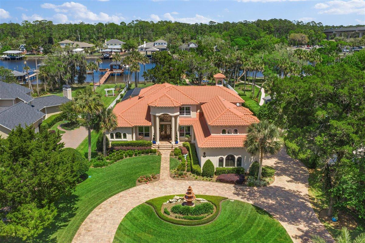 Rare opportunity - WATERFRONT 116 ft on Intracoastal Waterway. Over 1 acre on sought after West side of ICW.  This outdoor lover's paradise is perfect for entertaining with Eastern exposure in the back, boat lift, floating dock & heated screened in pool w/ spa. Park like setting w/ firepit, multiple outdoor seating areas & beautiful garden spaces. Primary suite, office, & guest ste on the main level. Large kitchen w/ 2 islands opens to family room w/ sliders leading out to spacious screened lanai. Upstairs are 3 more bedrooms, 2 baths, bonus room (currently home office with private entry & half bath) plus 2nd family room/game room. Custom built with stone & wood floors throughout lower level, LVT upstairs. Come see & enjoy this stunning property close to schools, sport fields & shopping. Preferred Membership Initiation Fee pricing for the clubs of Gate Hospitality - Ponte Vedra Inn & Club, The Lodge & Club, Epping Forest & The River Club - is available to the purchaser(s) of this property.