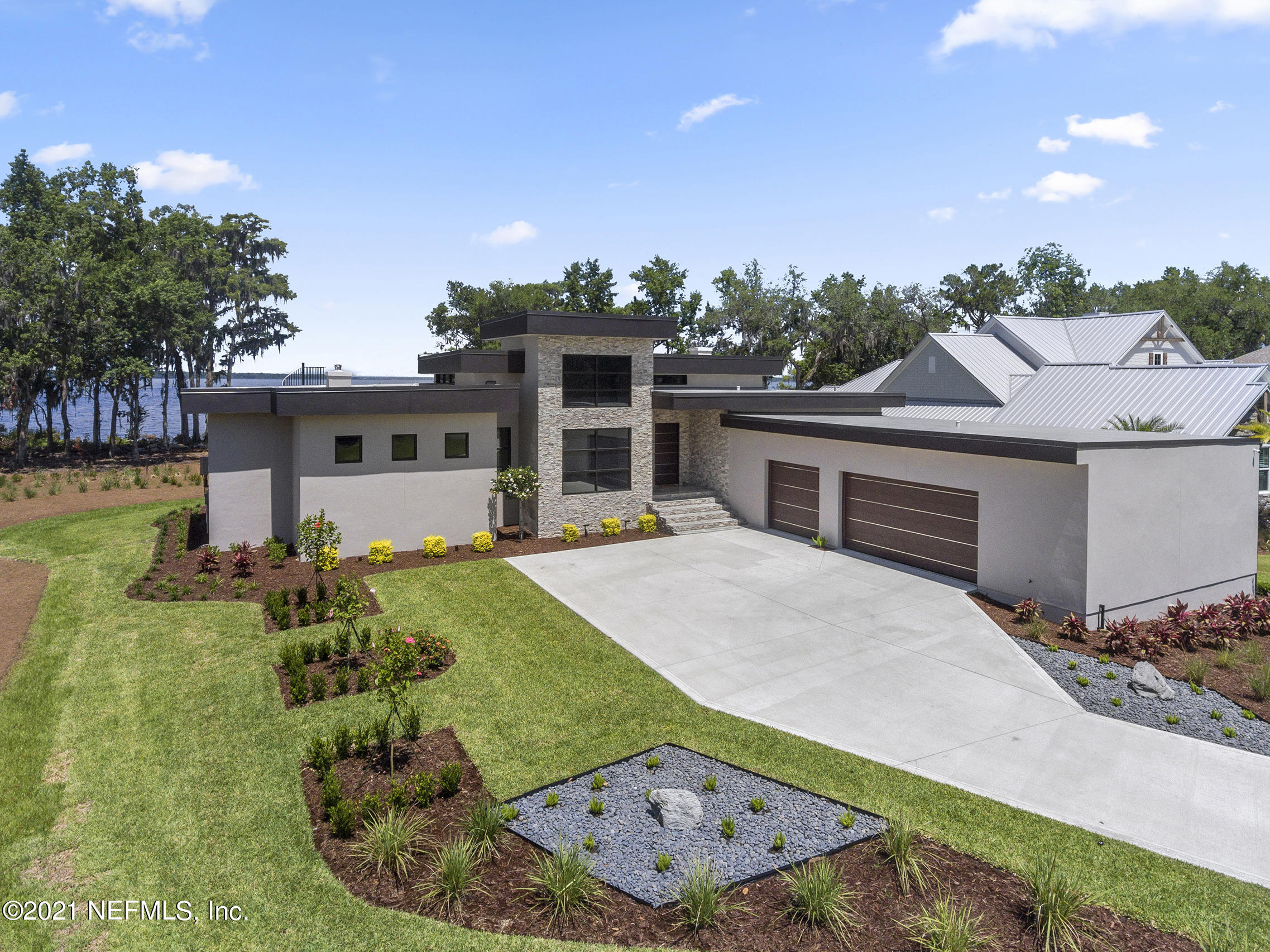 This Custom Contemporary River Retreat will impress the most discerning buyer with 350' of shoreline on the St. Johns River. CBS poured, Duro-last roof, commercial grade thermal impact resistant windows, whole home reverse osmosis, whole home generator, 1000 gal propane tank, 2 tankless water heaters, 2 linear gas fireplaces, Owners suite  fireplace is double sided.  Owner closet is dreamy. Chef's kitchen boasting high end appliances, double islands, impressive cabinetry, imported tile,  all with full river view, wait until you see the sunsets!  Superior craftsmanship/stonework, smart house. Winding staircase leads you to the rooftop area where your view is enhanced.  This space can be completed for entertaining. Simply one of a kind nestled  on a quite cul-de-sac street. Truly impressive