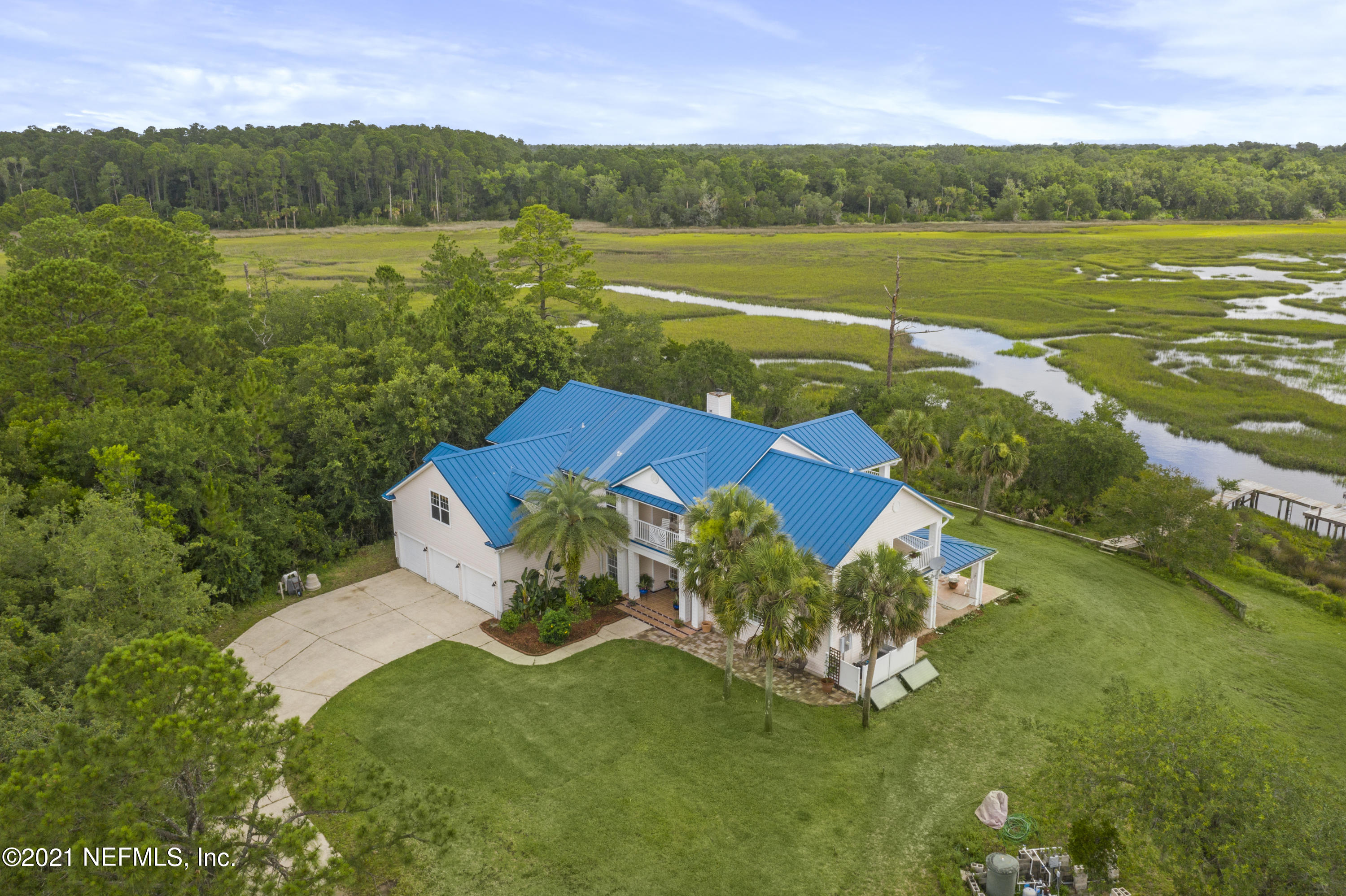 Spectacular home on over 8 acres of tidal water access close to Amelia Island & overlooking the St. Johns River Marshes Aquatic Preserve.15 min to Nassau River by boat.1,000 ft of tidal frontage, low tide 6 inches, high tide 6 feet on avg.Take the winding driveway through a canopy of oaks to find this private oasis. 95104 Mango Lane sits at an elevation of 16 feet, high and dry, NOT included in a flood zone. This 4,760 sq ft home boasts incredible views of wildlife, marsh and river from every single window. This home is perfect for everyone! The downstairs boasts an in-law suite complete with a kitchenette and living room space, as well as a private bedroom and en suite bath with ADA shower. A private office for those that require working from home or opt to home school. The family room is is a two story stunner! The natural sunlight pours in from every window making the space feel light, airy and open. The kitchen is updated with stainless steel appliances, a wine fridge, double oven and beautiful granite countertops. Head upstairs and find your guest bedrooms as well as your master suite. The master suite is on the opposite side of the home from the guest bedrooms. The master suite has an en suite bath with his & hers sinks, separate shower, garden tub and private commode. Enjoy a cup of coffee or a glass of wine on your balcony that overlooks the marsh. The guest bedrooms share a guest bath with two sinks and shower/tub combo, plus ample storage! Upstairs you will also find a huge bonus room (converted in 2019) perfect for games like ping pong & pool, plus great entertainment space for professional sports. Prefer to spend time outdoors, Mango Lane is your perfect home. With over 1900 ft of marsh views and tidal front you can fish, boat, paddle board, bird watch and so much more. Light up that fire pit and roast s'mores for the littles ones while you enjoy a cool libation. This property features enough land to build additional homes, boat houses, etc. as well as h