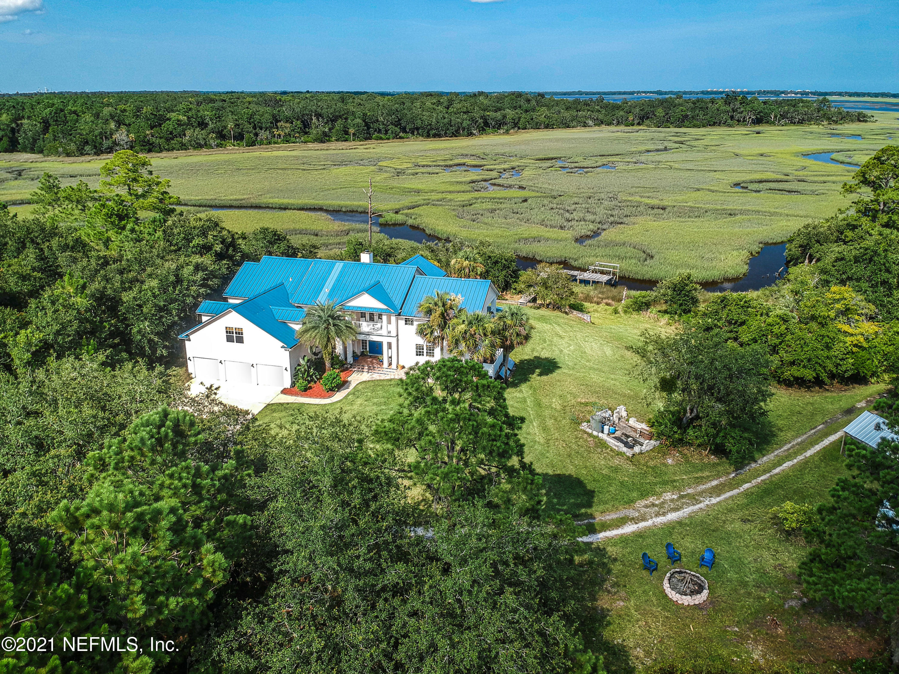 This 4,760 sq ft home with 5 acres has approximately 500 feet of marsh with tidal creek frontage and sits at an elevation of 16 ft, providing a high and dry sanctuary with exceptional & expansive views of the Nassau River, Amelia Island and is only 30 minutes to Jacksonville International Airport. Tide levels vary from 6 inches to over 6 ft. Shallow draft fishing or kayaking accessible from the dock or you can use two public boat ramps less than 2 miles away for deeper water. This property is not in a flood zone. With 5 bedrooms, 3.5 baths this home has a private ground floor guest or family member suite with kitchenette, living room, bedroom, walk-in closet, ADA shower room, linen closet and WC. The primary suite upstairs has panoramic views of the marsh and a private porch. Office or De downstairs, large flex or game room upstairs. The walkway that separates the primary side from guest side bedrooms is where the WOW factor comes in with stunning views and overlooking the great room below. 95104 Mango Lane is a perfect retreat, quiet and secluded with over 1700 sq ft of porches to relax or entertain. Light, bright and airy, the house boasts plenty of open space to gather or areas to retreat to when you need a bit of privacy. Wired for music inside and out. You can fish, kayak, paddle board, bird watch and so much more! Light up the fire pit and roast s'mores! This property features enough land to build an additional home, swimming pool, boat house, etc. Adjoining land to purchase is an option. Closets galore, you will not lack storage space. Well water- no city water bill. No HOA. Has septic and irrigation systems. A natural spring fed pond, dock, 3 bay garage, interior laundry and & water softener (conveys).