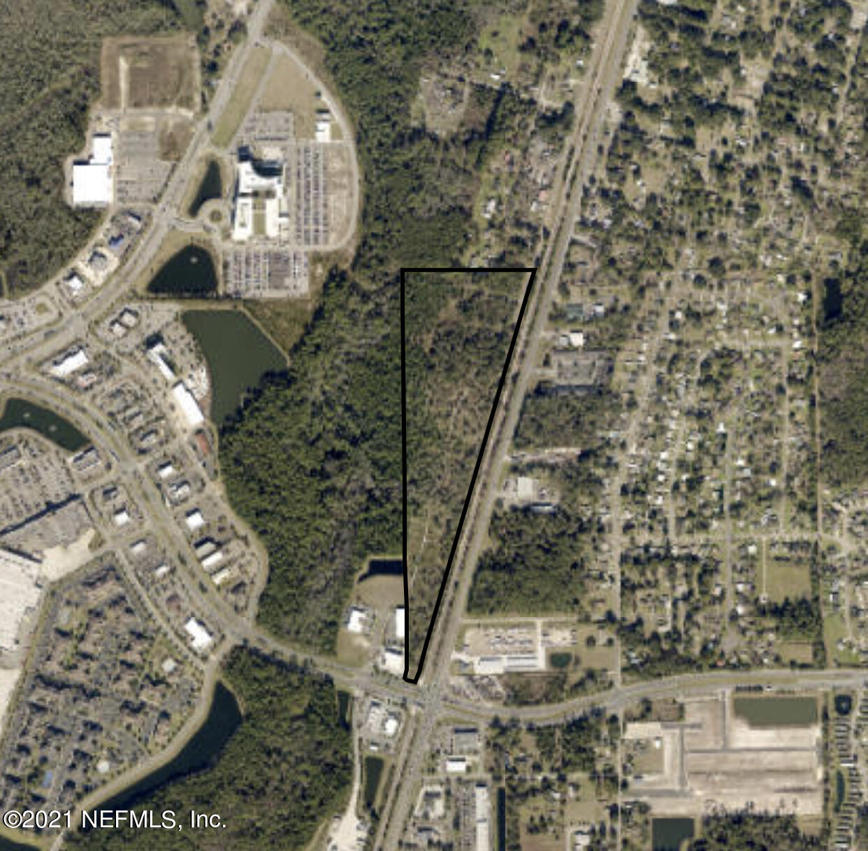 Triangular shaped parcel runs along the Seaboard Coastline Railroad, zoned Industrial Light.  Property use 5600 Timber SI 70-79.  Property has two points of access, from Wolf Bay Dr passing RPM Automotive then use of an easement or from the Residential street 1st Street West.