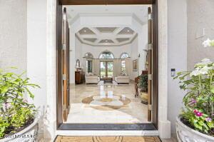 Double entry mahogany doors open into a Foyer. Custom travertine marble medallion in Foyer floor.