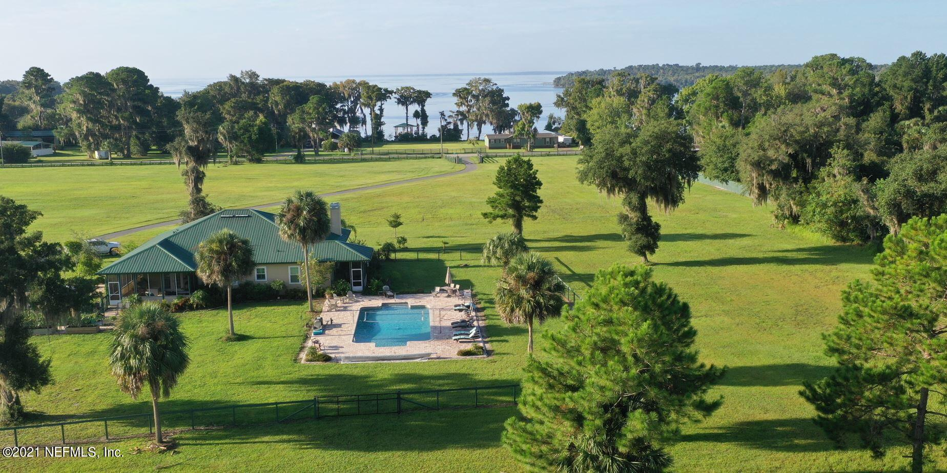 """GORGEOUS RIVERFRONT RESORT ON 41 ACRES WITH SPECTACULAR RIVER VIEWS! Enjoy horseback riding, ATV trail riding, swimming pool, fishing, boating & more on this self sustained homesteaded resort!! Luxurious 3BR home with high end upgrades on 19.96 acres PLUS a 19.96 acre pasture PLUS 1 acre on the St. Johns River! 2 stone fireplaces on 66x15 wrap around screened porch & comfy living room, both with wood floors & wood ceiling! Scrumptious kitchen with top of the line appliances! Huge dining room! Split bedroom plan with spacious owner suite with river views. 2nd bedroom has its own 15x10 screen porch with river views. Huge saltwater heated pool with river view! One acre sits directly on St Johns River with brand new dock, boat lift & boat house. 2 STEEL BUILDINGS - 50x30 PLUS 50x60 fits RV. Plus, a 3 Stall Barn for the horses & an adorable chicken coop. Plant a garden anywhere on this 41+acre property known to everyone as the """"RESORT Not only can you live off the land here, it's the perfect place to gather your friends. There are hookups available for 3 RV's!! Take your friends/family for an ATV ride through miles of trails, or jump on your boat & meet your friends at the springs! This wonderful home sits on 19.96 acres & joins another 19.96 acres of pasture! Ride your horses through acres of land on & around this homestead. To top it off, you've got an acre directly on Lake George which expands to St. Johns River where you can explore miles of river, lots of islands & the manatees at the springs. This home was built to create a self sustained homestead where you could, literally, live off the land & the river. Every single thing was done with that in mind, from the 2 huge steel buildings to the chicken coop, the 3 stall barn and the dock directly on the river. This is a luxuriously unique & stunning property that would be hard to duplicate! Close to St Augustine and Jacksonville!"""