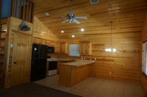 Kitchen area - all knotty pine cabinets .