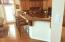 Granite bar and countertop, wood floors, plentiful natural light.