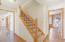 Hallway off office has stairway to upper level.