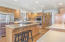 Kitchen features custom cabinets, stainless appliances, built in double convection wifi enabled ovens, center island with range, and pod lighting.