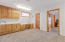 Lower level Arts & Crafts/Sewing Room has wall of storage cabinets and counter