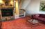 Spacious living room with hardwood floors under the carpeting with beautiful cozy brick fireplace