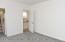 Door to hallway and walk in closet, with attic access.