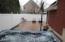 View from patio overlooking hot tub and yard