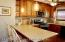Newly redone kitchen with eating island and pendant lighting.