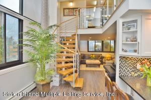Spectacular custom designed staircase to mezzanine level to 2 bedrooms, 1/2 bath & laundry/ storage room.