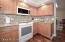 Kitchen features Oak cabinetry, Quartz counters, new appliances, glass backsplash