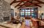 A beautiful two-sided stacked-stone fireplace, gleaming hardwood floors, and vaulted ceilings with exposed truss-work are a few of the architectural accents in the great room which spills out onto the large wrap-around patio.
