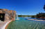 """Located at the edge of an expansive lake, the pool decks and swimming pool merge with the shoreline of the lake creating an """"infinity"""" edge. Faux boulders reinforce the illusion that the pool and lake are a single body of water, and also form """"grotto"""" areas for hot tubs. """"Lava tube"""" tunnels and a slide with waterfall provide enjoyable areas for children to explore in a lively family atmosphere. Expansive glass opens the exercise rooms up to the views of the lake and surrounding mountains."""