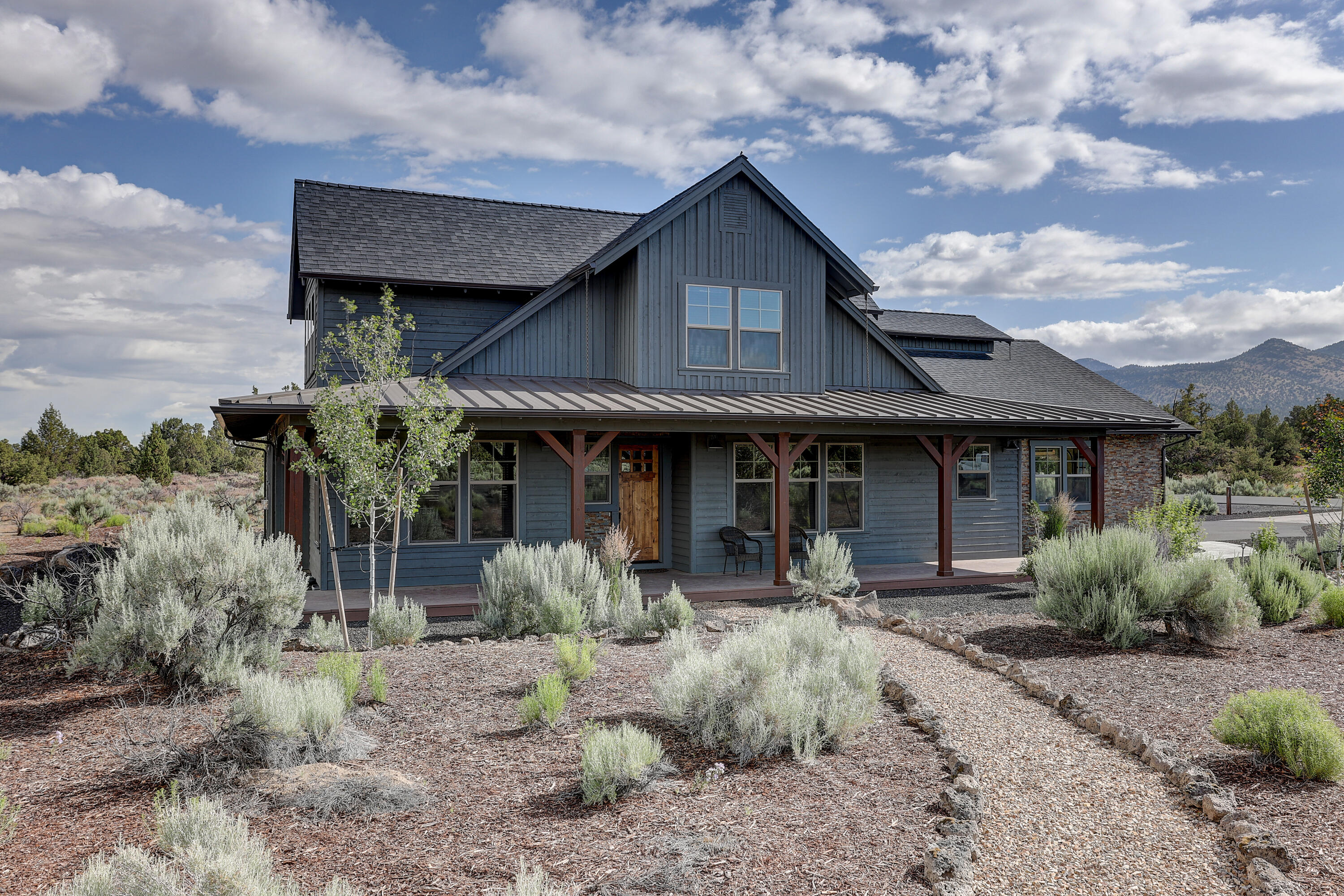 This beautiful ranch-style home welcomes you with a covered front porch into an open living space filled with wide-planked wood floors and natural wood trim. the light walls give a more current twist to this homestead. In the modern kitchen you'll find two granite islands, tons of storage, and a 5-burner gas stove top. The huge master bedroom is on the main with two walk-in closets and a master bathroom that includes a tile shower and soaking tub. The office, or 4th bedroom, includes built-in desk and wall bed for guests. the laundry room is filled with storage cabinets and utility sink. Upstairs features a bonus room, and 2 bedrooms, one with Cascade Mountain views. The 3-car garage has an extended length 2-car section and includes cabinets and work bench. Cozy up in front of the gas fireplace or relax on the back patio while enjoying the view of Powell Butte and acres of BLM land that the property backs to, instead of working on the low-maintenance natural landscaping.