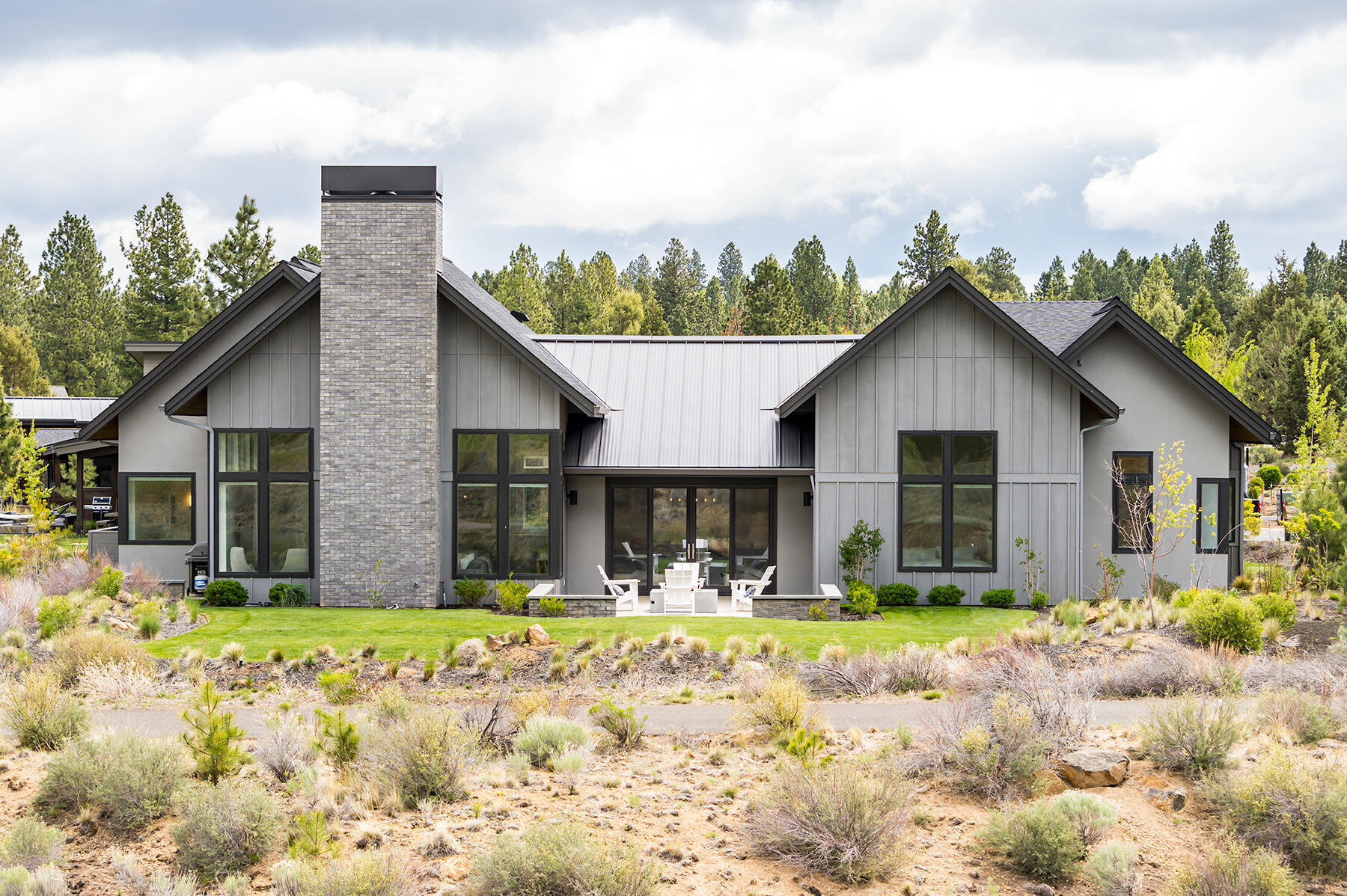 This beautiful modern farmhouse sits on a premium end of cul-de-sac level lot buffered by a large common area and set back from the 12th green at Tetherow, providing exceptional privacy and sweeping long range views of the high desert landscape and Cascade Mountains. Towering vaulted ceilings fill the home with natural light while the custom concrete and shiplap fireplace flanked by large windows takes center stage in the magazine-worthy great room. The carefully thought out floor plan lives like a single level home with 4 en-suite bedrooms, office and bonus room all on the main level.  The primary suite includes a spa-like bathroom with soaring ceilings and great separation from the additional bedroom suites. Two separate upstairs bonus areas provide flexibility in use or an ideal area for overflow guests with a full bathroom. Designer fixtures and finishes throughout provide luxurious yet comfortable living. This is Central Oregon living at its best!