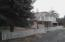 Gravel circular drive, metal carport by tree/white picket fence & attached Carport on other side of the house.