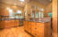 Open space and prep-service island in the bright and light kitchen with undermount lighting.