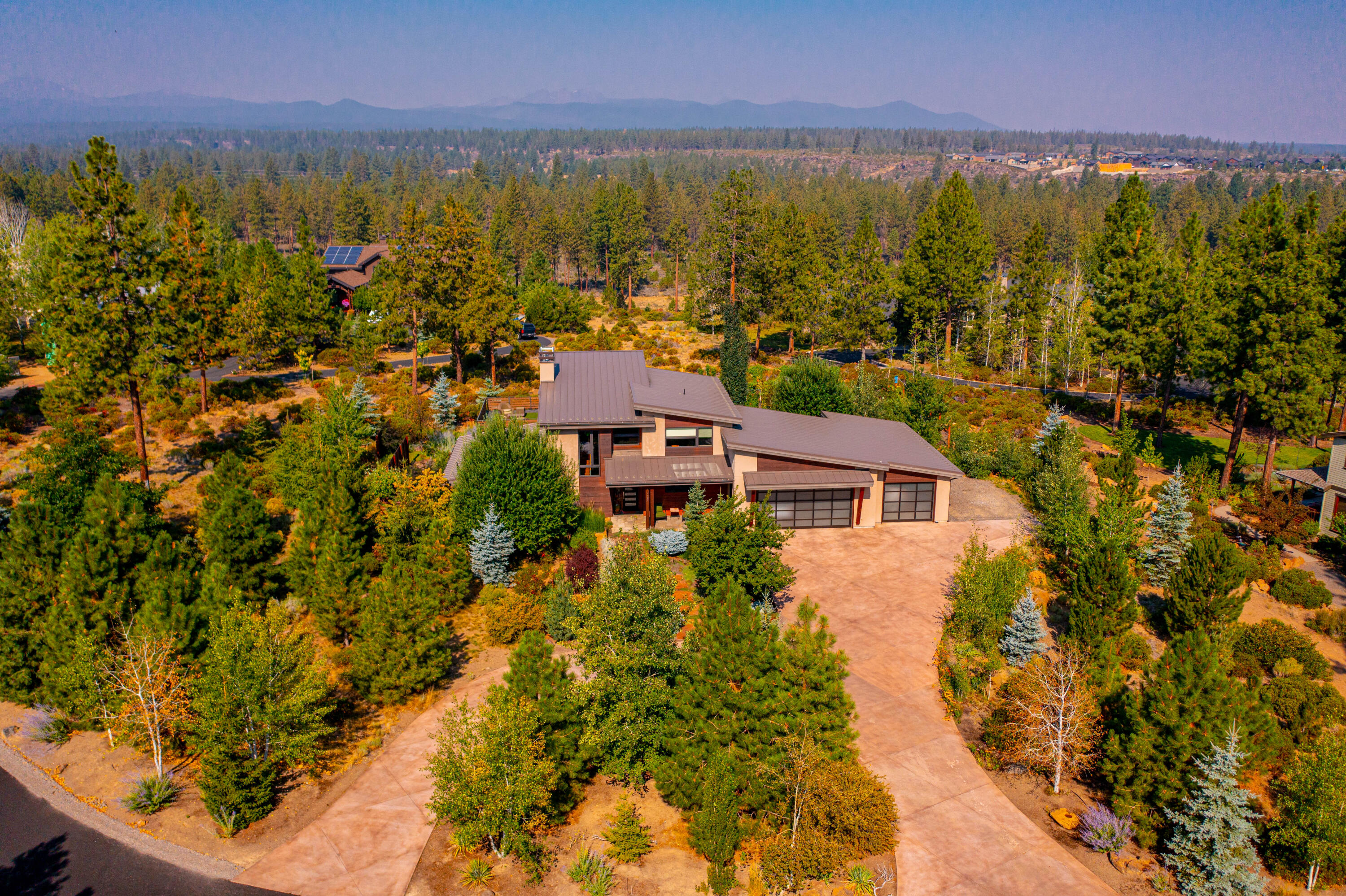 Architect designed by it's owner, this contemporary dream home gazes at the Cascade mountains on a private 1.42 acre lot overlooking professionally designed gardens and glass greenhouse. The home opens to hiking trails along the Deschutes River, mountain biking access to the Bend Trail system, paved bike path into Bend, and only 18 minutes to Mt. Bachelor and the Cascade Lakes.  Design features include 3 indoor fireplaces, 2 outdoor, Cement Elegance counters, expansive mud room with custom lockers and oversized 3 car glass door garage with shop area including 3 - 220V capability.  Designer kitchen features the largest island with built-in drawer fridges, Sapele wood and glass cabinets, 6 burner professional grade range - a chef's dream! Custom 8' Teak interior doors throughout home. Downstairs primary suite with heated bathroom floors in bathroom, and office makes for easy living while the upstairs features a great room, large upstairs deck with Cascade views, 2 bedrooms & a bathroom.