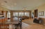 A large great room with amazing light fixtures and fans, plantation shutters, and modern open concept.